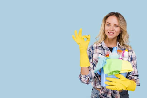 Professional showing ok sign while holding cleaning products buckets