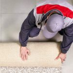 Professional worker unrolling carpet floor