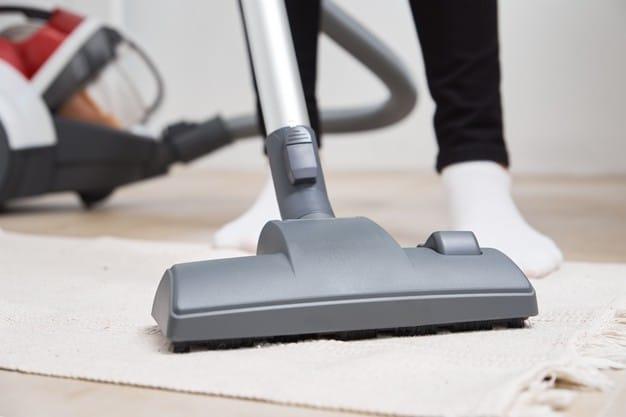 Woman using vacuum cleaning carpet rug