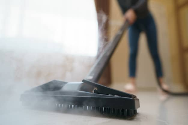 Woman washes floor with steam mop